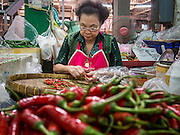 "23 AUGUST 2013 - BANGKOK, THAILAND:    A market vendor sorts chilies while she waits for customers at Pak Klong Talat in Bangkok. Thailand entered a ""technical"" recession this month after the economy shrank by 0.3% in the second quarter of the year. The 0.3% contraction in gross domestic product between April and June followed a previous fall of 1.7% during the first quarter of 2013. The contraction is being blamed on a drop in demand for exports, a drop in domestic demand and a loss of consumer confidence. At the same time, the value of the Thai Baht against the US Dollar has dropped significantly, from a high of about 28Baht to $1 in April to 32THB to 1USD in August.    PHOTO BY JACK KURTZ"