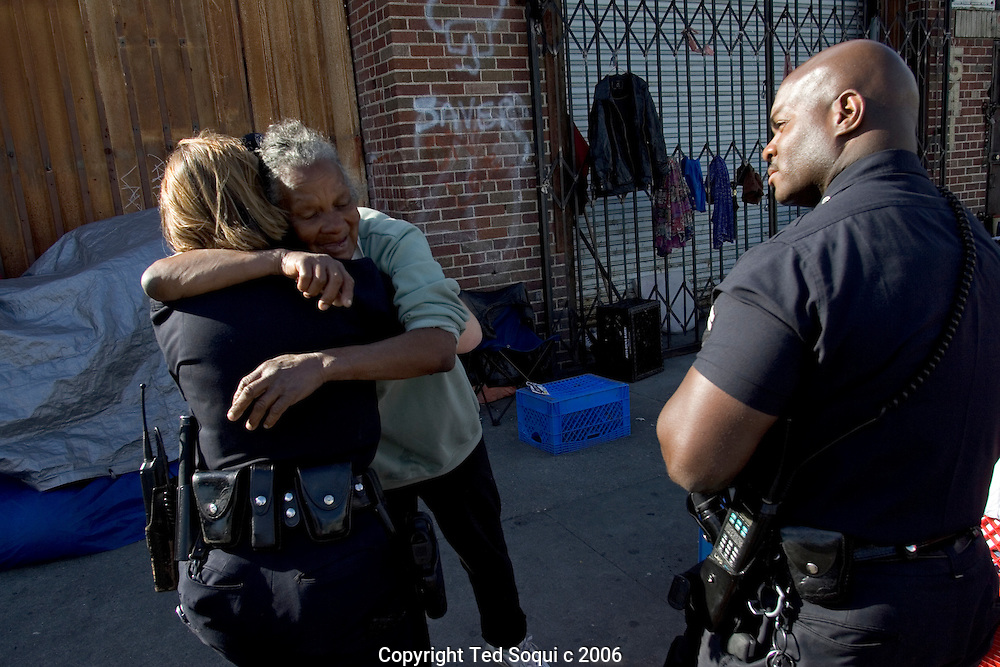 Senior Lead Officers Deon Joseph and Kathy McAnany receiving a hug from a homeless women on Los Angeles's skid row.