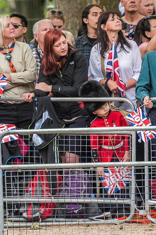 A young Guardsman peers from the crowd - Queens 90th birthday was celebrated by the traditional Trooping the Colour as well as a flotilla on the river Thames.