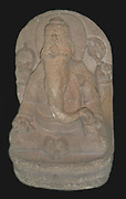 The Hindu god Ganesha (the elephant god). In his right hand the god of wisdom holds aset of prayer beads and his broken tusk. The left hand holds an axe and a bowl of sweetmeats. Eastern Javanese andesite stone sculpture. Indonesia. 13th century