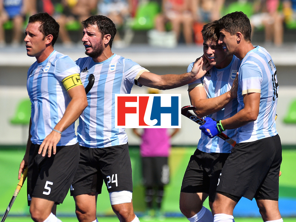 Argentina's Matias Rey (2nd R) celebrates with teammates Argentina's Ignacio Ortiz (R), Argentina's Pedro Ibarra (L) and Argentina's Manuel Brunet during the men's quarterfinal field hockey Spain vs Argentina match of the Rio 2016 Olympics Games at the Olympic Hockey Centre in Rio de Janeiro on August 14, 2016. / AFP / Carl DE SOUZA        (Photo credit should read CARL DE SOUZA/AFP/Getty Images)