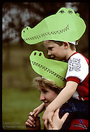 Riding mom's shoulders in Earth Day parade, son wears gator hat like mom's; Forest Park-St Louis Missouri