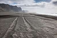 Ash from Volcano Eyjafjallajökull on the usually black sand beach of Vík, South Iceland. Tire tracks in the sand.