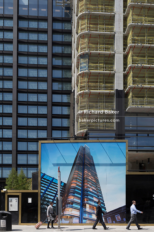 Passers-by and a construction hoarding showing the Foster-designed Principal Tower that's under construction on Shoreditch High Street, on 10th May 2017, in London, England.