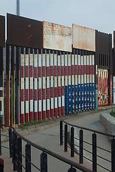 La bandiera degli USA interpretata sul muro della frontiera dalla parte del Messico. Le croci rappresentano i caduti nel tentativo di passare.