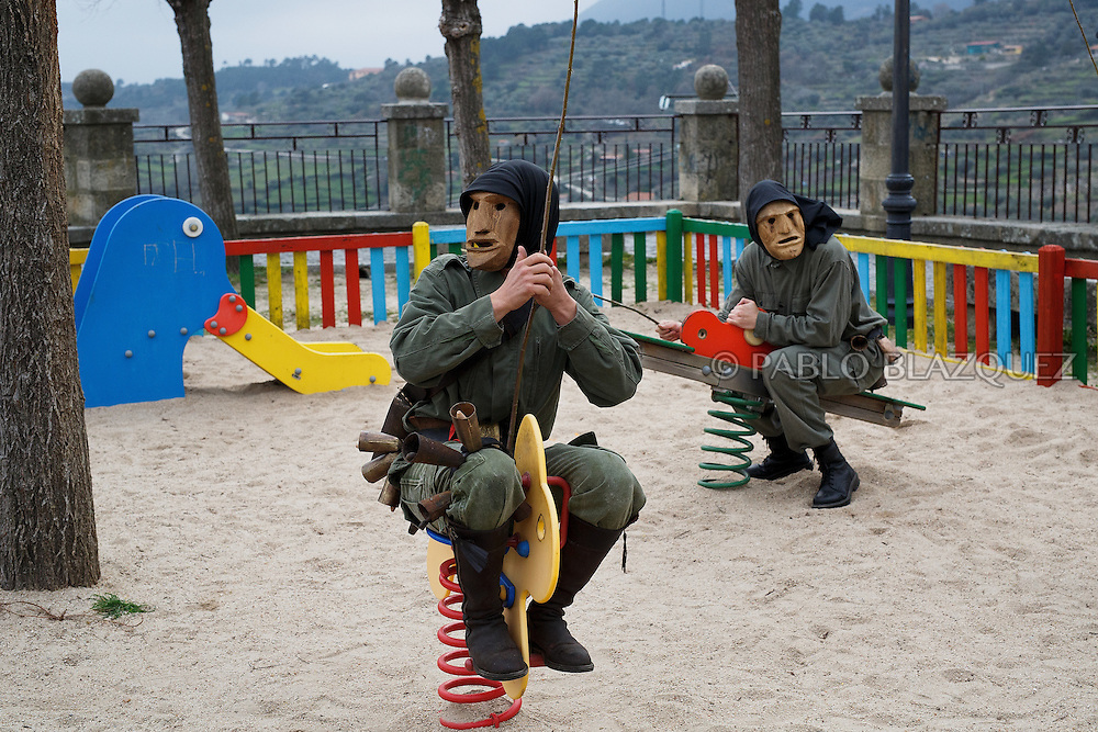 The Machurreros from Pedro Bernardo use children swings in a park during Carnival on February 6, 2016 in Pedro Bernardo, in Avila province, Spain. The origins of this pagan festival are unknown. The Machurreros wear wood masks, a military dress, black handkerchief, cowbells, and hold wicker stick. The festival disappeared after Dictator Franco forbid carnival festivals in 1937, but it was recently recovered. Before disappearing, male villagers after the military service, used to dress as Machurreros as they run along the streets scaring children and adults with their wicker stick to bring fertility to the land and expel the evil spirits. (© Pablo Blazquez)