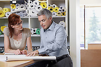 Man and woman studying paperwork in office