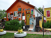"""The Heidelberg Project: Bringing Colour, Art, and Controversy to a Decaying Part of Detroit<br /> <br /> Watching the deterioration of his impoverished, crime-riddenneighborhood of McDougall-Hall two decades after Detroit's 1967 race riots, artist Tyree Guyton felt the need to do something. So he picked up a paintbrush and painted pastel polka dots all over his grandfather's Heidelberg Street house.<br /> Guyton's paint job was the first act toward what became the Heidelberg Project, an outdoor community art project aimed at breathing life back into his decaying district. Encouraged by his grandfather, and with the help of local kids, Guyton began decorating the abandoned homes beside the polka-dot house and installing art made from salvaged materials.<br /> The project now spans two blocks and is constantly evolving, anchored by the altered houses. One ramshackle two-story home is covered in stuffed animals. Another is painted with numbers of wildly varying sizes and colors. Strewn across the yards are sculptures incorporating decorated cars, shopping carts, doors, shoes, and household appliances.<br /> Though the infusion of color and creativity has attracted a stream of appreciative visitors to McDougall-Hall, the Heidelberg Project has some vocal critics. Chief among them is the city of Detroit, which demolished parts of the community in 1991 and 1999.<br /> Local detractors view the Heidelberg Project as an eyesore and health hazard, and resent the fact that it draws further attention to Detroit's urban blight. On November 12 of this year, the project's """"House of Soul,"""" an abandoned house decorated with hundreds of records, burned to the ground in a suspected arson attack. This followed a suspicious fire in May, in which an art-enhanced building called the """"Obstruction of Justice House"""" was destroyed.<br /> Undeterred, Guyton has responded to the destruction with relentless optimism and vowed to continue expanding his vibrant art community.<br /> <br /> •Visit """