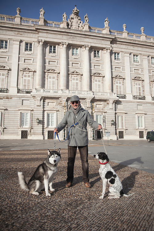 A man walks his dogs in front of the Royal Palace in Madrid, Spain.