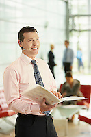 Businessman Holding Report and Using Wireless Headset