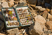 A fishermans open fly box filled with a variety of imitation flies on a rocky river bank. PLEASE CONTACT US FOR DIGITAL DOWNLOAD AND PRICING.