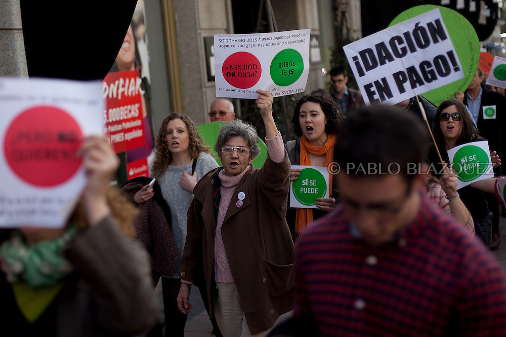 Anti eviction activists shout slogans and hold placards reading 'Yes we can, but they don't want' during an 'escrache' on their way to the house of Spain's President of Parliament Jesus Posadas on April12, 2013 in Madrid, Spain. The Mortgage Holders Platform (PAH) and other anti evictions organizations have been organizing 'escraches' for several weeks under the slogan 'There are lives at risk' to claim the vote for a Popular Legislative Initiative (ILP) to stop evictions and facilitate social rent, outside Popular Party deputies' houses and offices. 'Escraches' are a form of peaceful protest that were used in Argentine in 1995 to publically denounce pardoned members of the dictatorship for their crimes at their doorsteps.