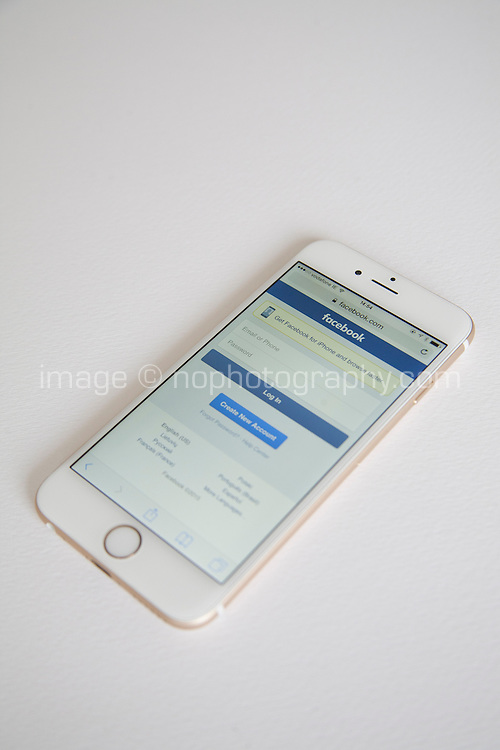 Gold and white Apple iPhone 6 with Facebook log in page against a white background