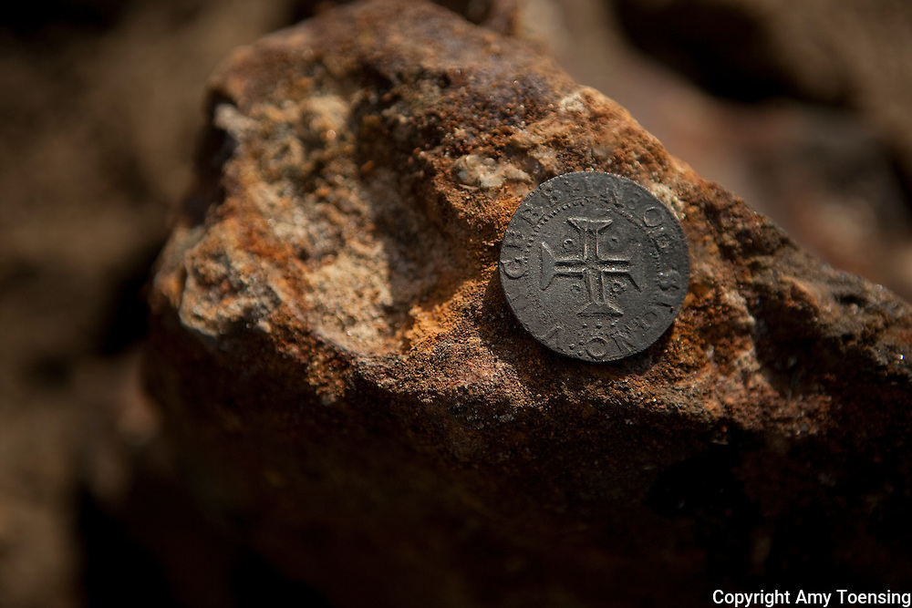 ORANJEMUND, NAMIBIA -- SEPTEMBER 24: A silver coin, from the the time of King John II's reign, found on site of the Portuguese shipwreck on September 24, 2008 in Oranjemund, Namibia. The wreck was discovered by miners in the Namdeb diamond mine off the coast of Namibia. The ship was found seven meters below sea level on April 1, 2008. Archeologists presume the wreck is from the early 1500s. Most of the the artifacts found are being stored in a storage shed at the Namdeb Diamond Mine. Items include: copper ingots, bronze canons, canon balls, pewter bowls and plates, ivory tusks from African elephants, and most substantial over 2000 gold coins- approximately 21 kg - the most gold found in Africa since the Valley of the Kings in Egypt. (Photo by Amy Toensing) _________________________________<br /> <br /> For stock or print inquires, please email us at studio@moyer-toensing.com.