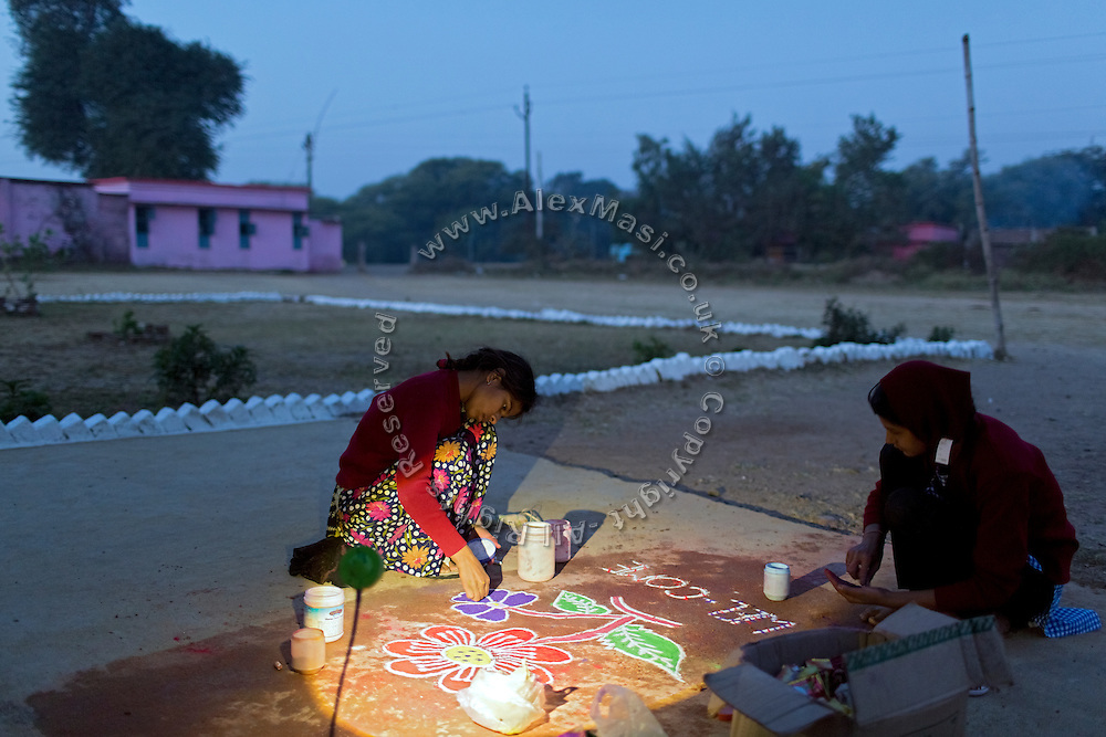 Two girls studying at the MS Jamoniya Tank Schhol, near Sehore, Madhya Pradesh, India, are preparing a welcoming Hindu 'rangoli' in the early hours of the morning, in front of the Jamoniya Tank Girls Hostel, where the Unicef India Sport For Development Project has started in 2012. Covering 313 state-run girls' hostels and 207 mixed hostels in Madhya Pradesh, the project ensures that children from Scheduled Tribes (ST) and others amongst the poorest people in India, can easily access education and be introduced to sports. Field workers from Unicef also oversee their nutrition and monitor the overall conditions of each pupil.