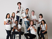 Group portrait of young photographers sitting on ladder and chairs
