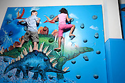 Two children rock climbing on an indoor wall