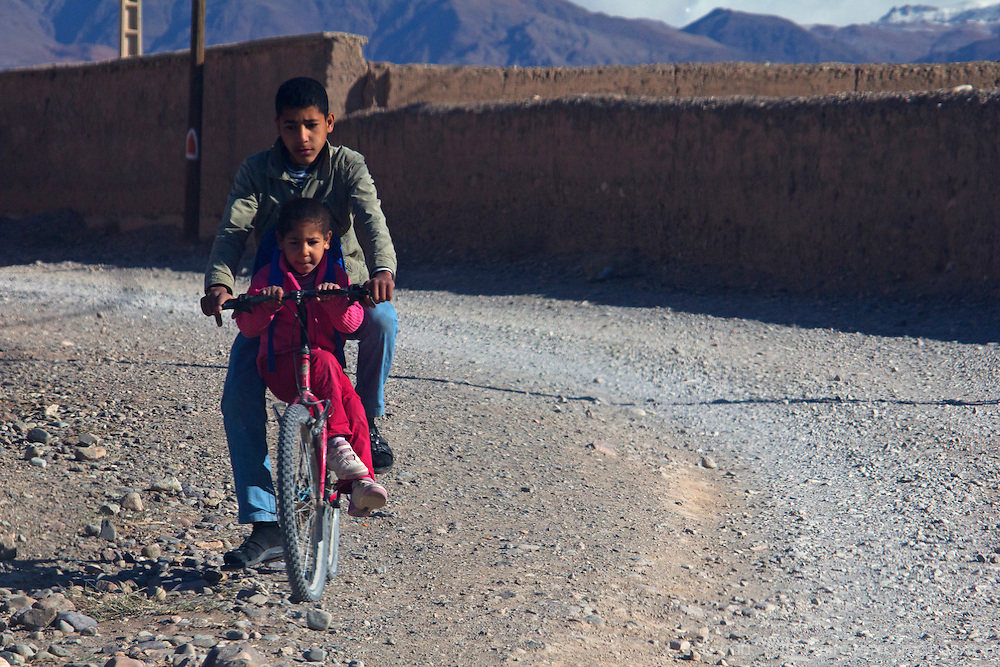 Africa, Morocco, Skoura. Kids on bike near Skoura.