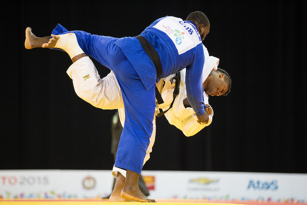 Freddy Figueroa of Ecuador (in white) throws Alex Garcia of Cuba in their men's judo +100kg class final of the table at the 2015 Pan American Games in Toronto, Canada, July 14,  2015.  AFP PHOTO/GEOFF ROBINS