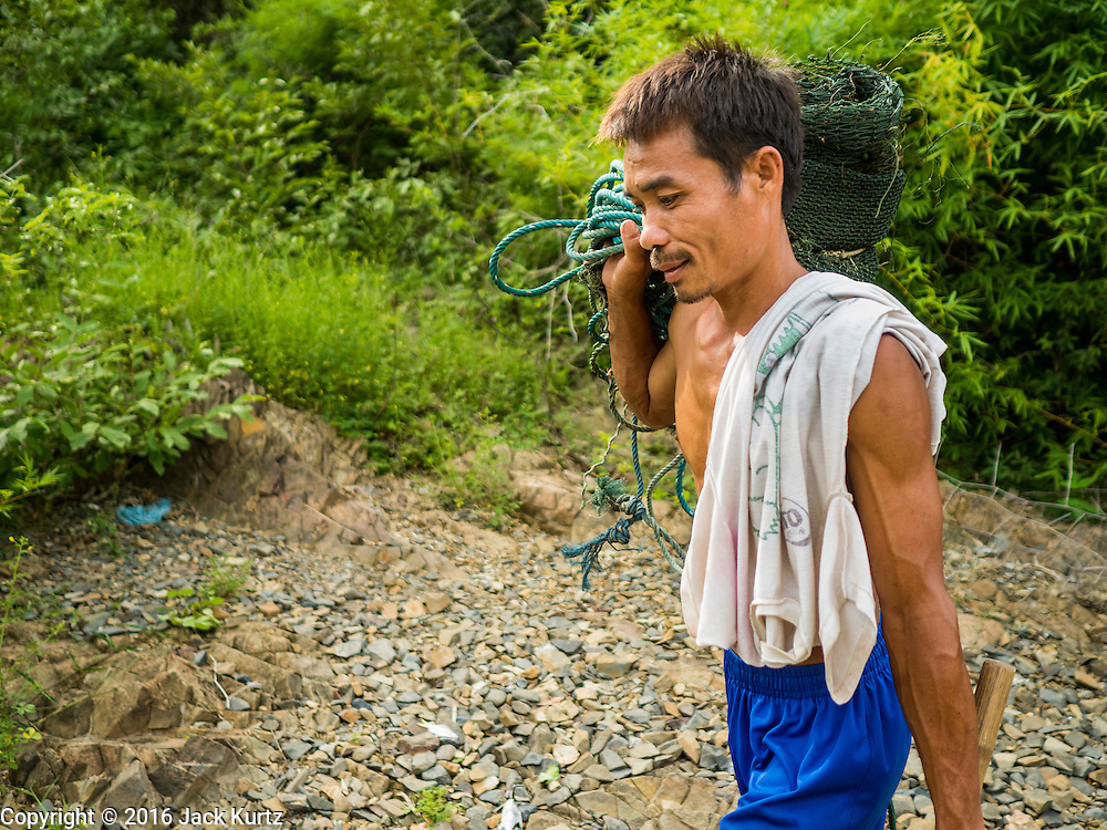 17 JUNE 2016 - DON KHONE, CHAMPASAK, LAOS:  A fisherman carries his equipment to a canoe near Khon Pa Soi Waterfalls, on the east side of Don Khon. It's the smaller of the two waterfalls in Don Khon. Fishermen have constructed an elaborate system of rope bridges over the falls they use to get to the fish traps they set. Fishermen in the area are contending with lower yields and smaller fish, threatening their way of life. The Mekong River is one of the most biodiverse and productive rivers on Earth. It is a global hotspot for freshwater fishes: over 1,000 species have been recorded there, second only to the Amazon. The Mekong River is also the most productive inland fishery in the world. The total harvest of fish from the Mekong is approximately 2.5 million metric tons per year. By some estimates the harvest in the Tonle Sap (in Cambodia) had doubled from 1940 to 1995, but the number of people fishing the in the lake has quadrupled, so the harvest per person is cut in half. There is evidence of over fishing in the Mekong - populations of large fish have shrunk and fishermen are bringing in smaller and smaller fish.        PHOTO BY JACK KURTZ