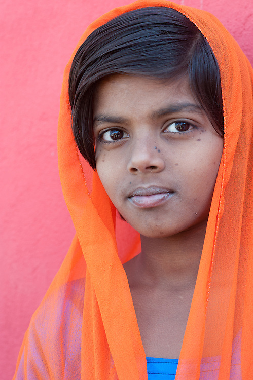Portrait of a young Indian girl wearing an orange dupatta (headscarf), India.