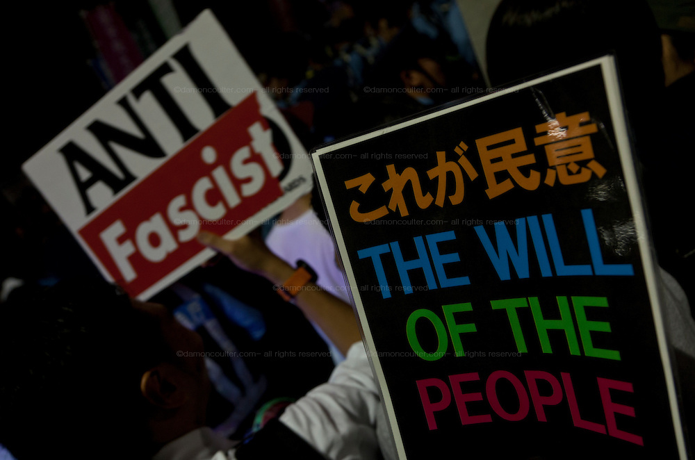 Signs at a protest against the revision of article 9 of the Japanese Constitution outside the Prime-Minister's house in Kasumigasaki, Tokyo, Japan. Monday June 30th 2014. Over 10,000 people showed their support for Japan's unique peace constitution and called on the government to halt its reinterpretation of Article 9 allowing Collect Self Defence which is expected to become law on July 1st