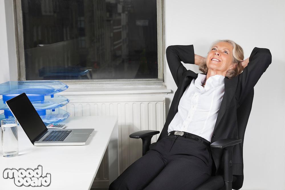 Smiling senior businesswoman relaxing at desk in office