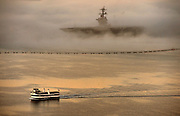 A ferry passes by as the USS Ronald Reagan (CVN 76) is enveloped in fog rolling in from the Pacific Ocean as she sits at her berth in San Diego, Calif., Feb. 11, 2014. DoD Photo By Glenn Fawcett (Released)