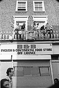 People standing on balcony on top of B&B food shop, Notting Hill Carnival, London, 1989