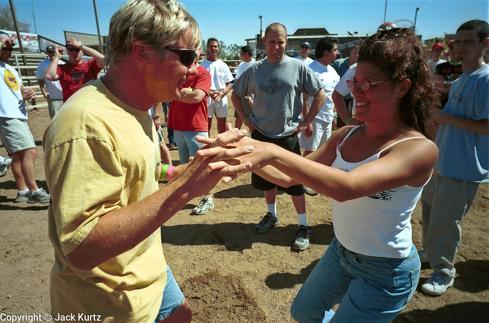 05 MAY 2002 - SCOTTSDALE, ARIZONA, USA: A couple dances before participating in the 1st Annual Running of the Bulls at Rawhide in Scottsdale, Arizona, Sunday, May 5, 2002. The event was a part of a Cinco de Mayo celebration. About 400  people paid up to $80 each to run with the bulls. The event was fashioned after the running of the bulls in Pamplona, Spain. .PHOTO BY JACK KURTZ