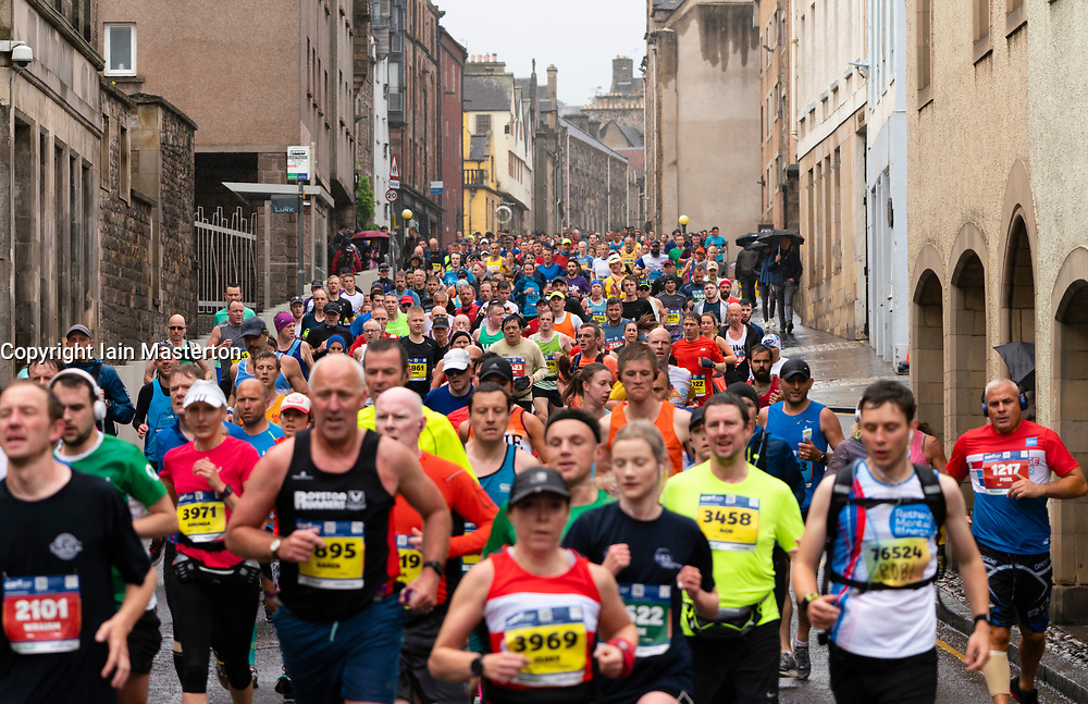 Edinburgh, Scotland, UK. 26 May, 2019. Many runners taking part in the Edinburgh Marathon Festival Marathon run down the Royal Mile in Edinburgh's Old Town towards Holyrood.