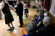 A woman chatting during the dancing at a St. Andrew's dinner dance held by the Sandbach and District Caledonian Society at Sandbach Town Hall, Cheshire, England on St. Andrew's Day. Around 40 people from the Society attended the meal and dance which included a programme of Scottish country dancing. St. Andrew was the patron saint of Scotland and the day was celebrated by Scots worldwide on the 30th November.