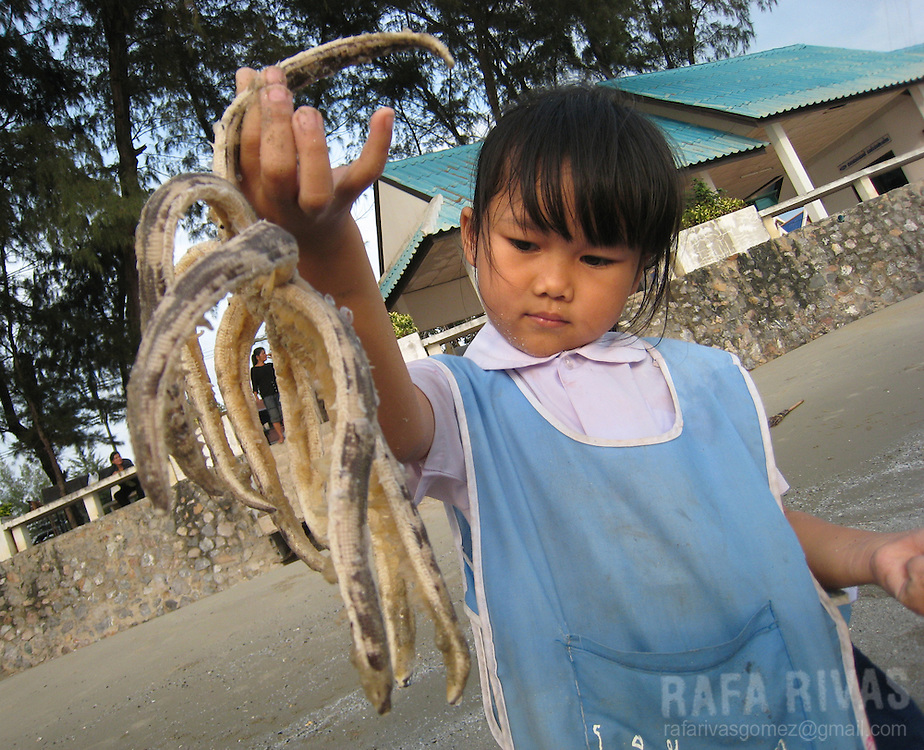 A little Thai girl poses as she holds a starfish at a beach in Thailand.