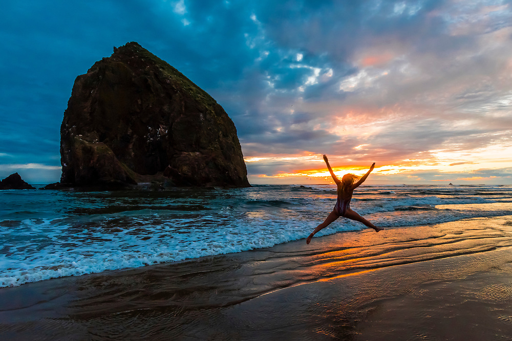 A teenaged girl playing in the surf jumps in front of Haystack Rock, Cannon Beach, Oregon USA.