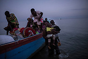 SEBAGORO, UGANDA - MARCH 23: Congolese refugees exit a boat after landing in Sebagoro, Uganda on March 23, 2018. Violence in Ituri Province in northeastern Democratic Republic of Congo has displaced more than 100,000 people including approximately 40,000 refugees who have fled to Uganda. (Photo by Andrew Renneisen for The Washington Post)