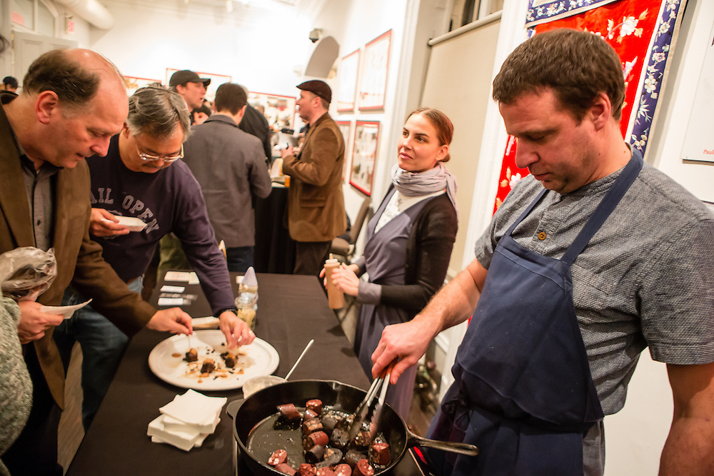 Flushing, NY - February 25, 2017. Huge Dufour from M Wells Steakhouse in Long Island City, Queens, cooking blood sausage at the 2017 Charcuterie Masters at Flushing Town Hall.