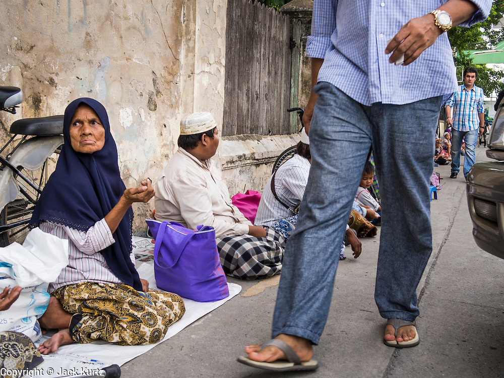"08 AUGUST 2013 - BANGKOK, THAILAND: Thai Muslims wait to receive ""zakat"" or alms from Muslims walking into Haroon Mosque in Bangkok to celebrate Eid al-Fitr. Eid al-Fitr is the ""festival of breaking of the fast,"" it's also called the Lesser Eid. It's an important religious holiday celebrated by Muslims worldwide that marks the end of Ramadan, the Islamic holy month of fasting. The religious Eid is a single day and Muslims are not permitted to fast that day. The holiday celebrates the conclusion of the 29 or 30 days of dawn-to-sunset fasting during the entire month of Ramadan. This is a day when Muslims around the world show a common goal of unity. The date for the start of any lunar Hijri month varies based on the observation of new moon by local religious authorities, so the exact day of celebration varies by locality.      PHOTO BY JACK KURTZ"