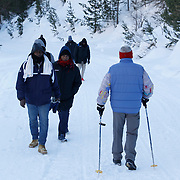 Abdullhai, 38 (L), and Abdurahman, migrants from Guinea walk along with another group as they pass an Italian man during an attempt to cross part of the Alps mountain range from Italy into France, near the town of Bardonecchia in northern Italy, December 21, 2017. Abdullhai and Abdurahman are two of hundreds of migrants who over the last year have attempted to cross from Italy into France through high mountain passes, in a bid to evade increased border security put in place at easier crossing points.