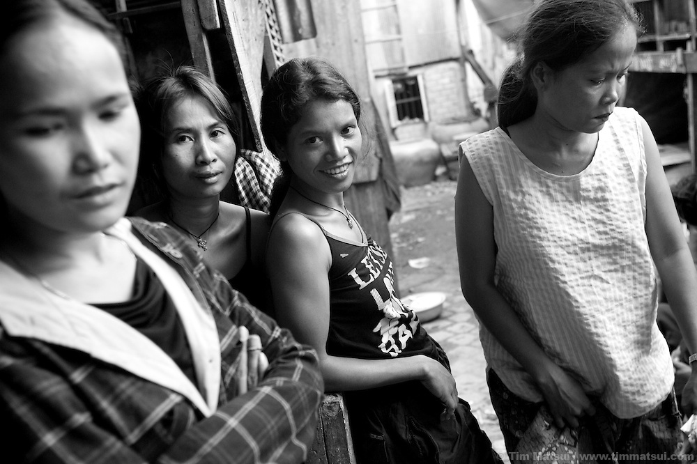 "Prostitutes Srey Leat, left, Srey Dah, center, and Srey Bee, right,  relaxing before a night of work while at home in the slum where the non governmental organization ""Acting for Women in Distressing Situations"" (AFESIP), conducts outreach and provides services in Phnom Penh, Cambodia. The permanent structure, a decaying four story building known simply as 'The Building', was built in the 1960's as transitional housing and now hosts a shantytown where many of the city's poor live, including many prostitutes, and is believed to have the highest rate of HIV infection in the city. AFESIP hands out free condoms, instructs prostitutes on HIV prevention, and conducts outreach in case the prostitutes need medical services, choose to leave their profession, or can report on cases of sex trafficking. AFESIP offers housing, education, training, and counseling for women who are victims of sex trafficking, worked as prostitutes, or are escaping domestic violence. Founded by Somaly Mam, who herself was once a prostitute and victim of trafficking and domestic abuse, AFESIP has three facilities in Cambodia and works with other NGO's to provide long term care for the women."