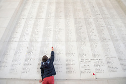 Pic Shows A young boy placing a poppy by the names on the Menin Gate memorial.<br /> The Duke of Edinburgh at the Menin Gate in Ypres, Belgium, at a ceremony on Armistice Day to mark the gathering of soil for the Flanders Fields Memorial Garden at the Guards Museum in London, United Kingdom. Monday, 11th November 2013. Picture by i-Images
