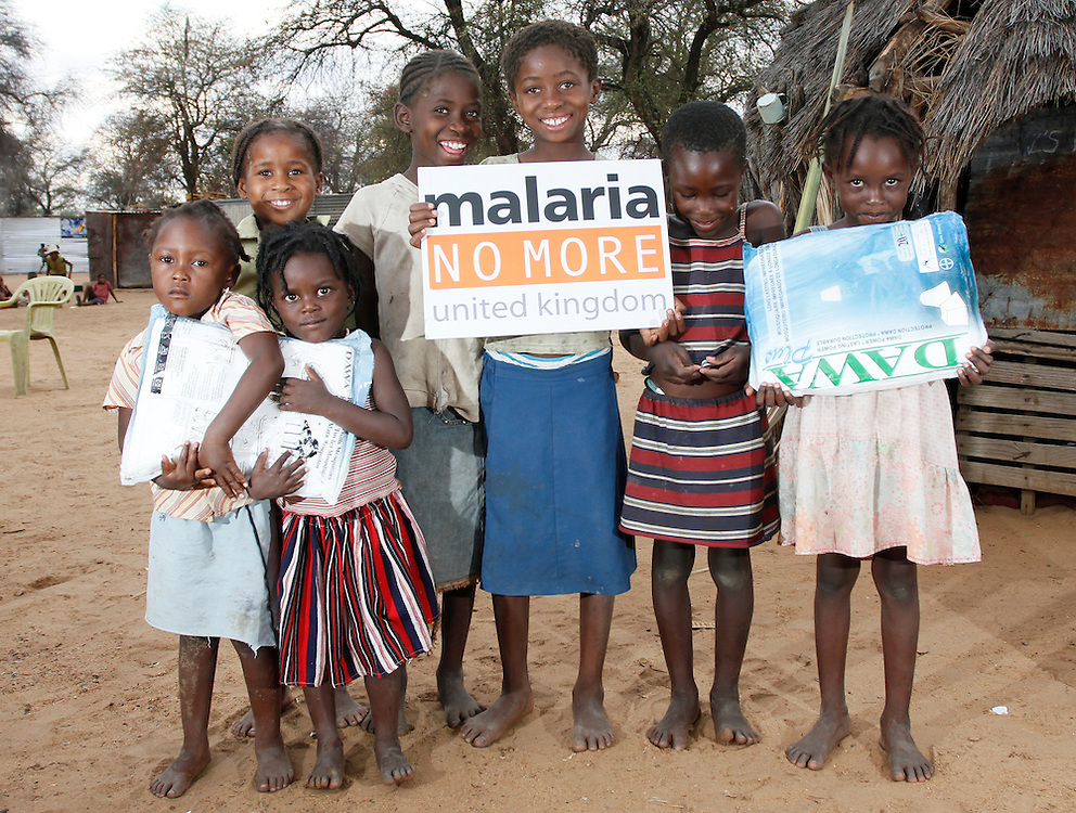 Children from the Fillipus family holding the Malaria No More UK sign. Malaria Agents with Nets for Life distributing mosquito nets in Oshivelo district, Northern Namibia. Malaria No More/UK