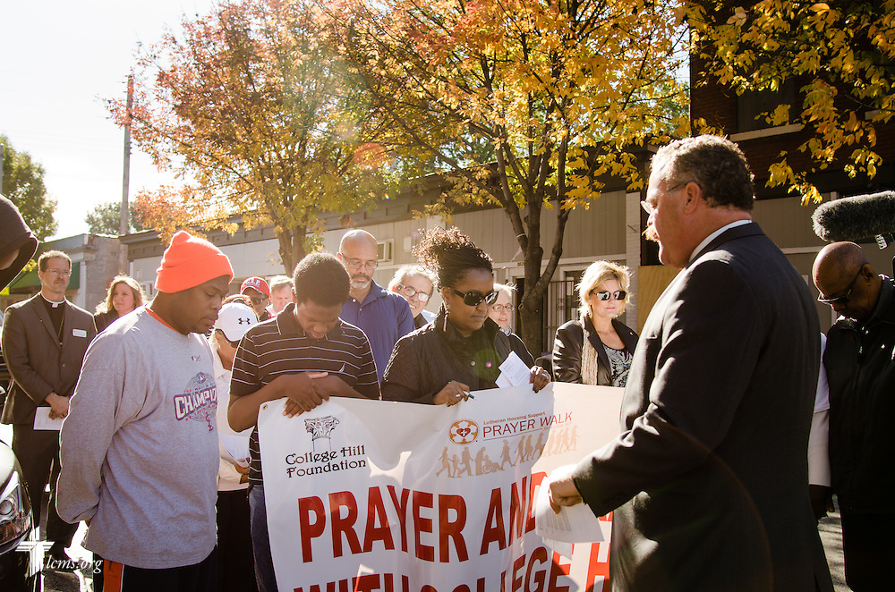 LCMS President Rev. Dr. Matthew C. Harrison and those who participated in the LCMS Prayer & Praise Walk on Friday, Oct. 17, 2014, in the College Hill neighborhood of St. Louis, stopped to pray for a College Hill resident (in orange hat). LCMS Communications/Frank Kohn