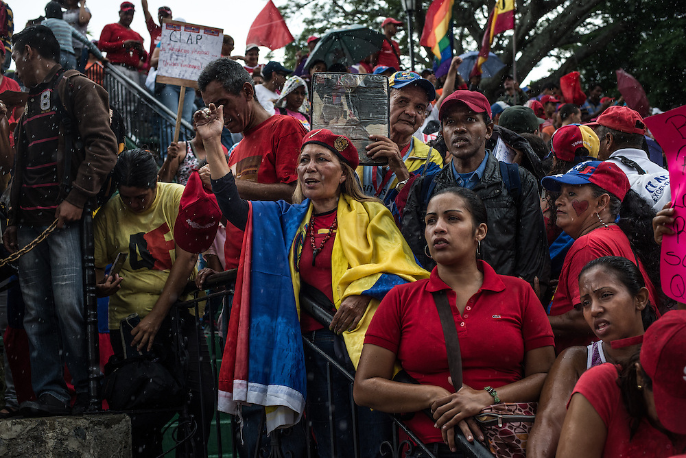 "CARACAS, VENEZUELA - JUNE 8, 2016: Loyalists to Venezuela's ruling socialist party who were given control of distributing government price-controlled food, participate in a rally in pouring down rain, by invitation of the President, at Miraflores, the presidential palace. Years of economic mismanagement, along with oil prices which fell to lows this year, have shattered Venezuela's food supply. In response, President Nicolás Maduro tightened has tightened his grip over the food supply. Using an emergency decree he signed in April, the president put most food distribution in the hands of a group of citizens brigades called C.L.A.P., loyal to leftists,  a measure critics say is reminiscent of food rationing in Cuba. ""They're saying, in other words, you get food if you're my friend, if you're my sympathizer,"" said Roberto Briceño León, director of the Venezuelan Violence Observatory, a human rights group. PHOTO: Meridith Kohut"