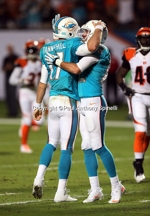 Miami Dolphins quarterback Ryan Tannehill (17) gets a celebratory pat on the helmet from Miami Dolphins wide receiver Brian Hartline (82) after Tannehill runs a quarterback sneak for a second quarter touchdown and a 7-3 lead during the NFL week 9 football game against the Cincinnati Bengals on Thursday, Oct. 31, 2013 in Miami Gardens, Fla.. The Dolphins won the game 22-20 in overtime. ©Paul Anthony Spinelli