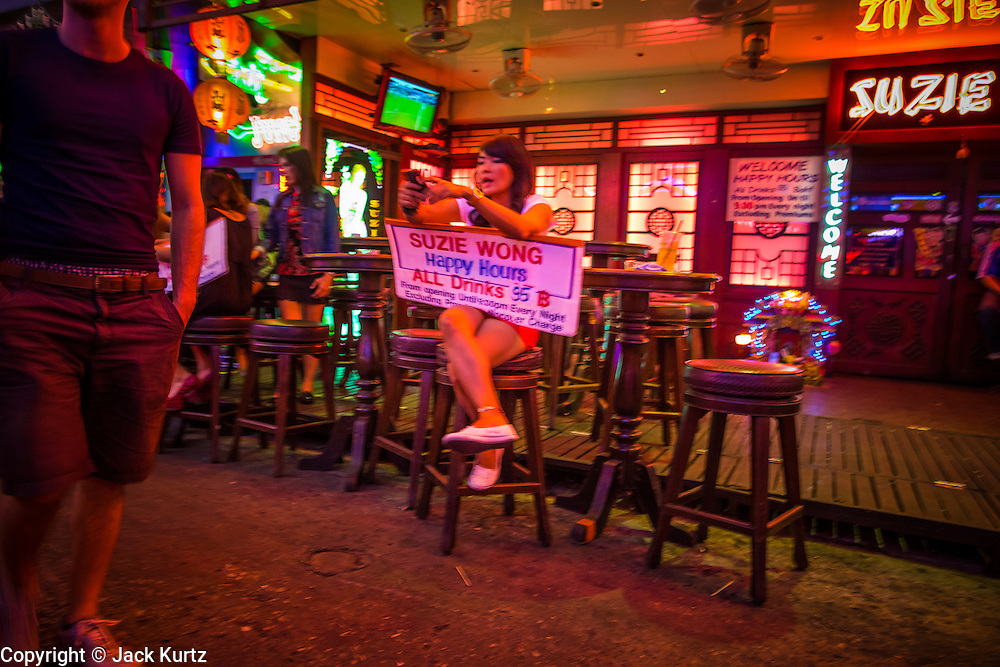 "12 JANUARY 2013 - BANGKOK, THAILAND:  A tout tries to draw tourists into Suzie Wong, a go-go bar on Soi Cowboy in Bangkok. Prostitution in Thailand is illegal, although in practice it is tolerated and partly regulated. Prostitution is practiced openly throughout the country. The number of prostitutes is difficult to determine, estimates vary widely. Since the Vietnam War, Thailand has gained international notoriety among travelers from many countries as a sex tourism destination. One estimate published in 2003 placed the trade at US$ 4.3 billion per year or about three percent of the Thai economy. It has been suggested that at least 10% of tourist dollars may be spent on the sex trade. According to a 2001 report by the World Health Organisation: ""There are between 150,000 and 200,000 sex workers (in Thailand).""    PHOTO BY JACK KURTZ"