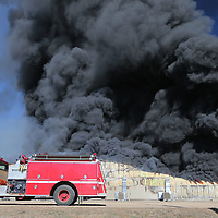 Volunteer firemen begin to assemble at the south end of American Furniture on Friday as they try and stop a fire from spreading to the few remaining building at their facility in Ecru.