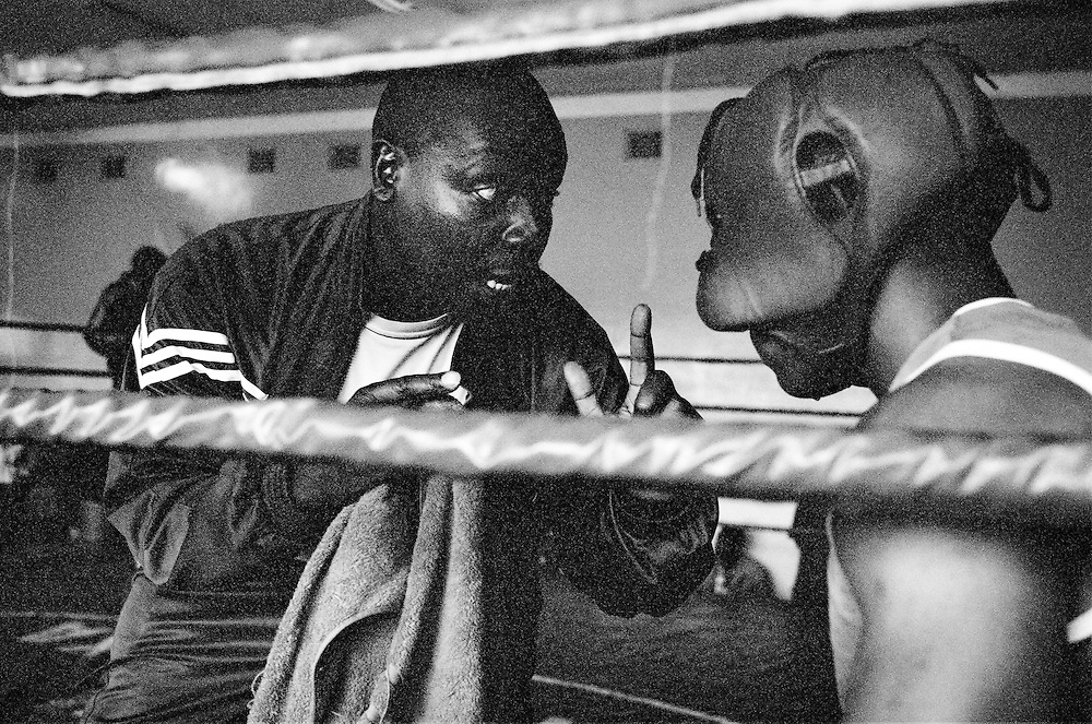 NAIROBI, KENYA - MARCH 18, 2010: A coach preps an athlete between rounds during a boxing tournament featuring the Kibera Olympic Boxing Club, Kenya Prisons and the Kenya Police and Armed Forces (AFABA). Each year, Kibera Olympic boxers aspire individually to make the national team, and the opportunity to compete in the annual Kenya Open boxing tournament. In previous years, boxers from Kibera slum have gone on to win tournaments on both the national and international stage.<br /> <br /> Within Kenya's progressive youth culture is the Kibera Olympic Boxing Club, a group of low-income adolescents from the slum whose leader uses boxing as a way to engage with idle youth. The group's ethnic diversity is remarkable given Kenya's 2008 post-election violence in which people from several tribes were forced violently out of slums. Together, these boxers represent a nascent trend of cross-tribe brotherhood in a healing nation.
