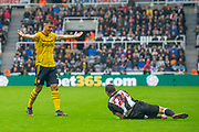 Granit Xhaka (#34) of Arsenal FC queries why Miguel Almiron (#24) of Newcastle United FC has gone down injured during the Premier League match between Newcastle United and Arsenal at St. James's Park, Newcastle, England on 11 August 2019.