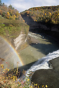 "Middle Genesee Falls rainbow, Portage Canyon, Letchworth State Park, Portageville, New York, USA. In Letchworth State Park, renowned as the ""Grand Canyon of the East,"" the Genesee River roars northeast through a gorge over three major waterfalls between cliffs as high as 550 feet, surrounded by diverse forests which turn bright fall colors in the last three weeks of October. The large park stretches 17 miles between Portageville and Mount Morris in the state of New York, USA. Drive or hike to many scenic viewpoints along the west side of the gorge. The best walk is along Gorge Trail #1 above Portage Canyon from Lower Genesee Falls (70 ft high), to Inspiration Point, to Middle Genesee Falls (tallest, 107 ft), to Upper Genesee Falls (70 ft high). High above Upper Falls is the railroad trestle of Portageville Bridge, built in 1875, to be replaced 2015-2016. Geologic history: in the Devonian Period (360 to 420 million years ago), sediments from the ancestral Appalachian mountains eroded into an ancient inland sea and became the bedrock (mostly shales with some layers of limestone and sandstone plus marine fossils) now exposed in the gorge. Genesee River Gorge is very young, as it was cut after the last continental glacier diverted the river only 10,000 years ago. The native Seneca people were largely forced out after the American Revolutionary War, as they had been allies of the defeated British. Letchworth's huge campground has 270 generously-spaced electric sites."