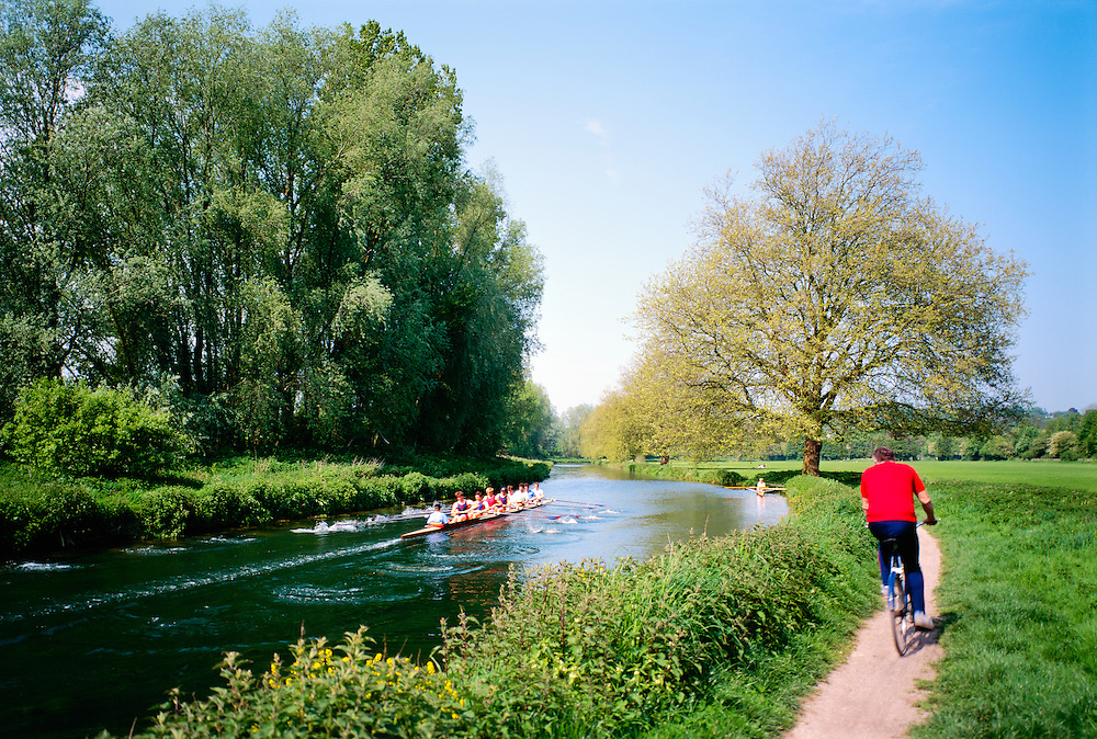 8 man rowing boat scull crew with cox and coach on bicycle train on the River Itchen at Winchester, Hampshire, England. Summer.